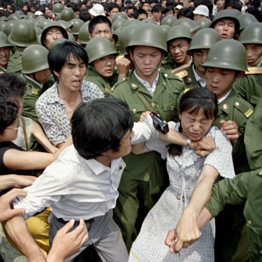 A young woman is caught between civilians and Chinese soldiers, who were trying to remove her from an assembly near the Great Hall of the People the day before the massacre.