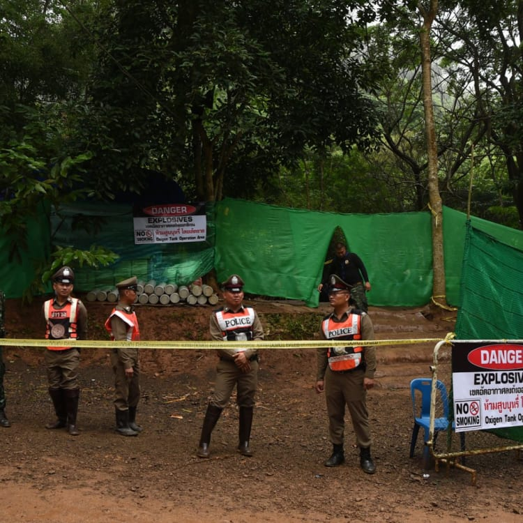 Thai police guard the entrance to the track leading to Tham Luang cave.