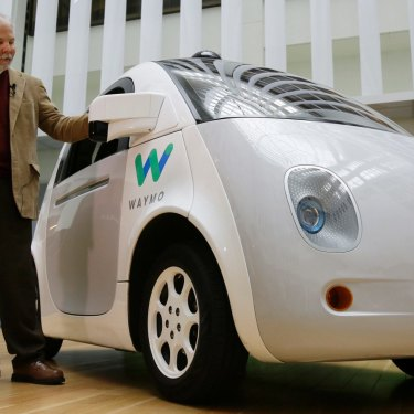 Steve Mahan, who is blind, stands by the Waymo driverless car during a Google event,