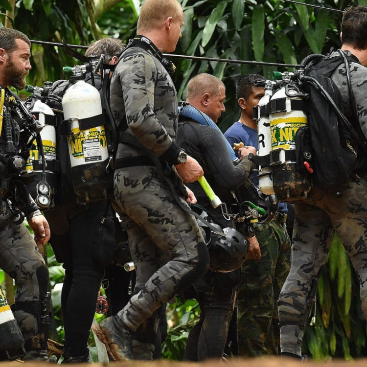 Members of the Australian dive team walk down the track that leads to the cave entrance on July 5.