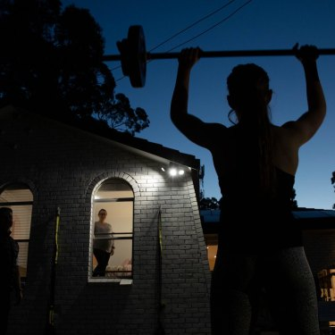 Fitness trainer, Chris Thomas, conducts training sessions in his front yard. His eight-month pregnant wife, Michelle, watches safely from the window.