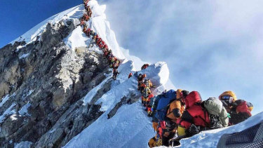 Mountain climbers lining up to stand at the summit of Mount Everest this climbing season.
