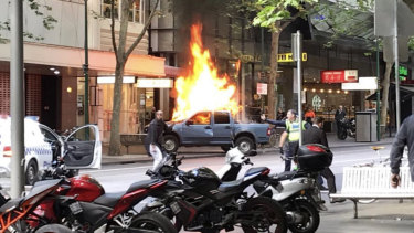 Police confront a man after a vehicle burst into flames on Bourke Street.