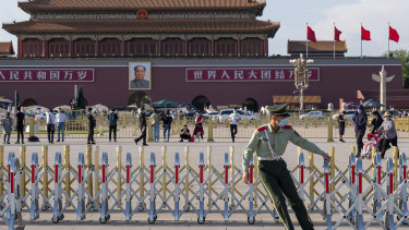 A member of the People's Armed Police sets up barriers in Tiananmen Square ahead of the national flag lowering ceremony.