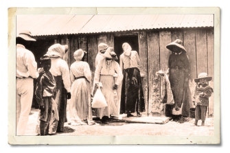 People lining up for flour rations at the Barambah Aboriginal Settlement (now known as Cherbourg) in Queensland in 1911.