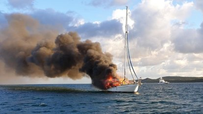 Two people, dog escape burning yacht near Moreton Island