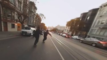 "Skateboarders ""bomb"" down one of San Francisco's notoriously steep hills."