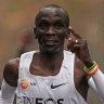 Eliud Kipchoge approaches the finish line, with his pacemakers celebrating behind.
