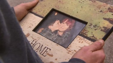 Harley holds a photo of himself with his mother Jenny Hayes.