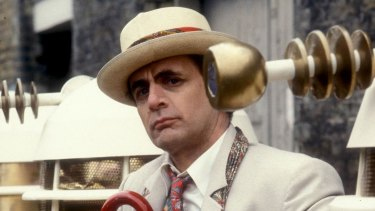 Sylvester McCoy's seventh Doctor Who flanked by his greatest enemy, the Daleks.
