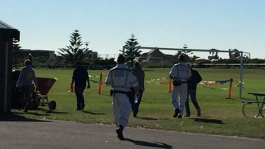Mystery: Police and a camera crew head towards bushland near Corroba Oval, in Stockton, on Tuesday morning investigating the suspected murder of Steven Fenwick.