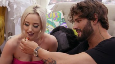Sam feeding Elizabeth chocolate-covered strawberries so she won't try to kiss him.