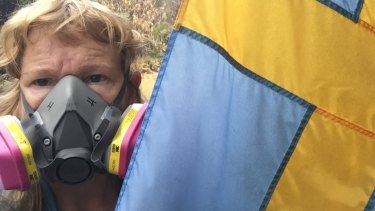 Helena Brandfors, at her house in Leilani Estate, protects herself from toxic fumes from the erupting Kilauea.