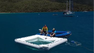 Coral researchers from the Great Barrier Reef Foundation move a coral embryo nursery into position in the Whitsundays.