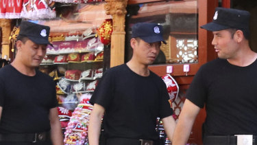Police officers patrol at a street in Urmuqi, the capital city of the Xinjiang Uyghur Autonomous Region (XUAR), in northwestern People's Republic of China.