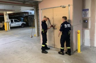 Firefighters use bolt cutters during an inspection of the Auburn apartment tower in late 2019.