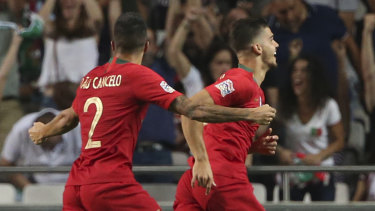 Victory: Portugal's Andre Silva (right) celebrates his goal against Italy.