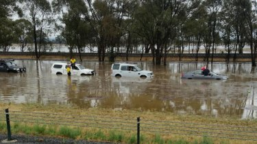 Passengers were seen sitting on the roofs of cars stranded on the Hume Freeway between Springhurst and Wangaratta as the state was hit by heavy rain.