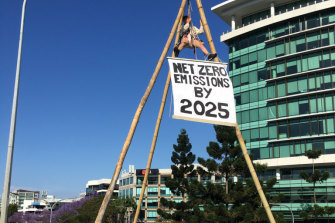 Extinction Rebellion activist Rilka is suspended from a bamboo tripod over a Milton motorway bypass in Brisbane, blocking traffic on Wednesday morning.