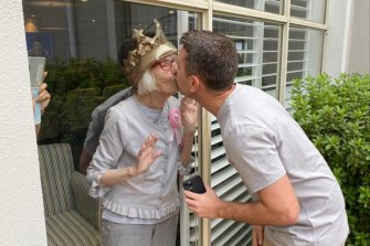 Gladys Nutbean kisses her grandson Sam Nutbean through her window on her 100th birthday on Friday.