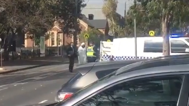 The man is taken into custody outside St Mary's Anglican Church in North Melbourne.