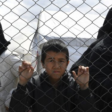 Foreign IS wives and children at the fence line of the Foreign section of al- Hawl camp in Syria, in April.