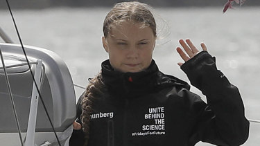 Climate change activist Greta Thunberg waves from the Malizia II boat in Plymouth, England.