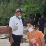 A woman has her temperature checked on the beach in Timor-Leste after arriving by boat.