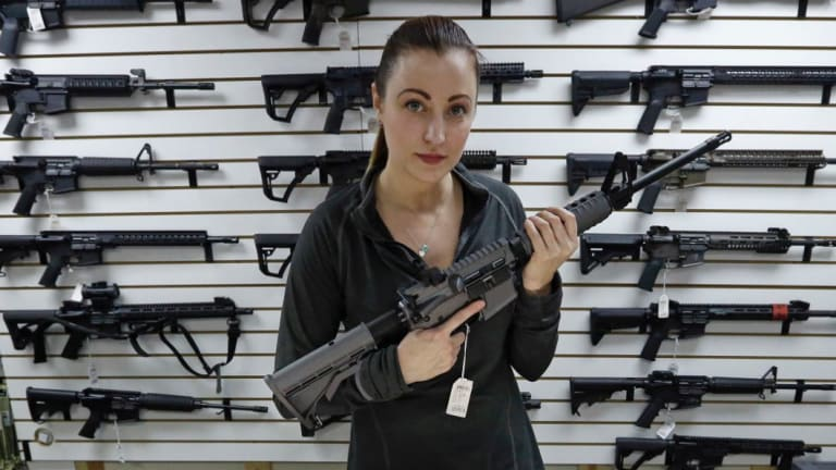 Gun shop owner Tiffany Teasdale-Causer poses for a photo with a Ruger AR-15 semi-automatic rifle, in 2017. The same model had been used by the shooter in a Texas church massacre two days earlier.