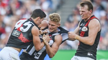 Adam Treloar wrestles with Bombers Connor McKenna and Brendon Goddard during a 2016 Anzac Day clash.