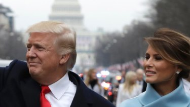 President Donald Trump waves as he walks with first lady Melania Trump during the inauguration parade on Pennsylvania Avenue in Washington.