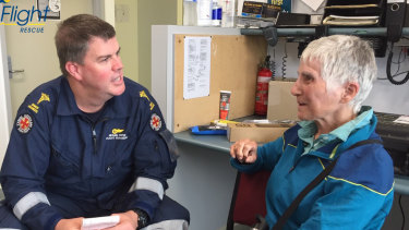 Madeleine Nowak with a paramedic after being retrieved from Fraser Island by the LifeFlight helicopter.