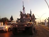 IS fighters in a commandeered Iraqi security forces armoured vehicle parading down a road in Mosul back in 2014.