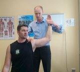 Chiropractor Nicholas Shannon assesses a patient's shoulder.
