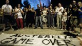 """Supporters of the """"OXI"""" or """"No"""" vote stand by an anti-austerity banner as they celebrate results in Thessaloniki."""