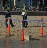 Police with the box of remains found on the St Kilda foreshore.