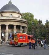 A fire truck is parked at the entrance to Parc Monceau.  The lightining strike left an adult and three children fighting for their lives.