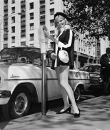 A 1960s meter maid feeds a parking meter in central Melbourne.