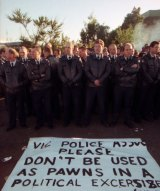 A line of Victorian police officers stand in front of a sign made by picketers asking them not to become involved in the dispute. Swanson Dock, Melbourne. April 18, 1998.
