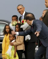 An aide directs children to look at cameras after they presented Barack Obama with flowers at Bole International Airport in Ethiopia.