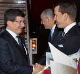 Turkey's Prime Minister Ahmet Davutoglu shakes hands with Queensland's Attorney-General Jarrod Bleijie upon arrival at the G20 Terminal in Brisbane.