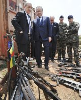 French President Francois Hollande, second from left, and French Defence Minister Jean-Yves Le Drian, left, inspect weapons confiscated by the French military during operation Sangaris, Central African Republic.
