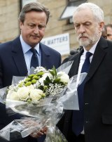 Britain's Prime Minister David Cameron, left, and Labour Party leader Jeremy Corbyn lay floral tributes in Birstall, northern England, for Jo Cox.