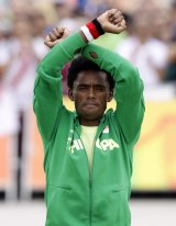 Silver medallist Feyisa Lilesa repeated his protest on the podium.