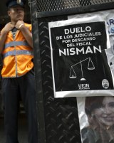 A police officer stands guard in front of the prosecutor's, where a sign is posted about the staff mourning the death of Alberto Nisman.