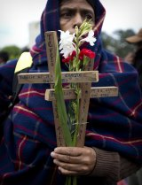 An indigenous woman holds wooden crosses and flowers on the National Day of Dignity for the Victims of Armed Internal Conflict in Guatemala City last week.