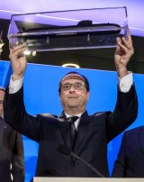 French President Francois Hollande shows a model of a submarine at DCNS headquarters in Paris on Tuesday.
