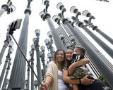 Marjorie Mabini takes a selfie with her niece Jaydah Mabini and son Jaren in front of the Urban Light installation at the Los Angeles County Museum of Art.