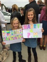 Mia Cooper, 7, with her big sister Ella, 9 wait to meet Prince Harry.