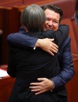 Liberal senator Dean Smith hugs senator Penny Wong after introducing the bill.